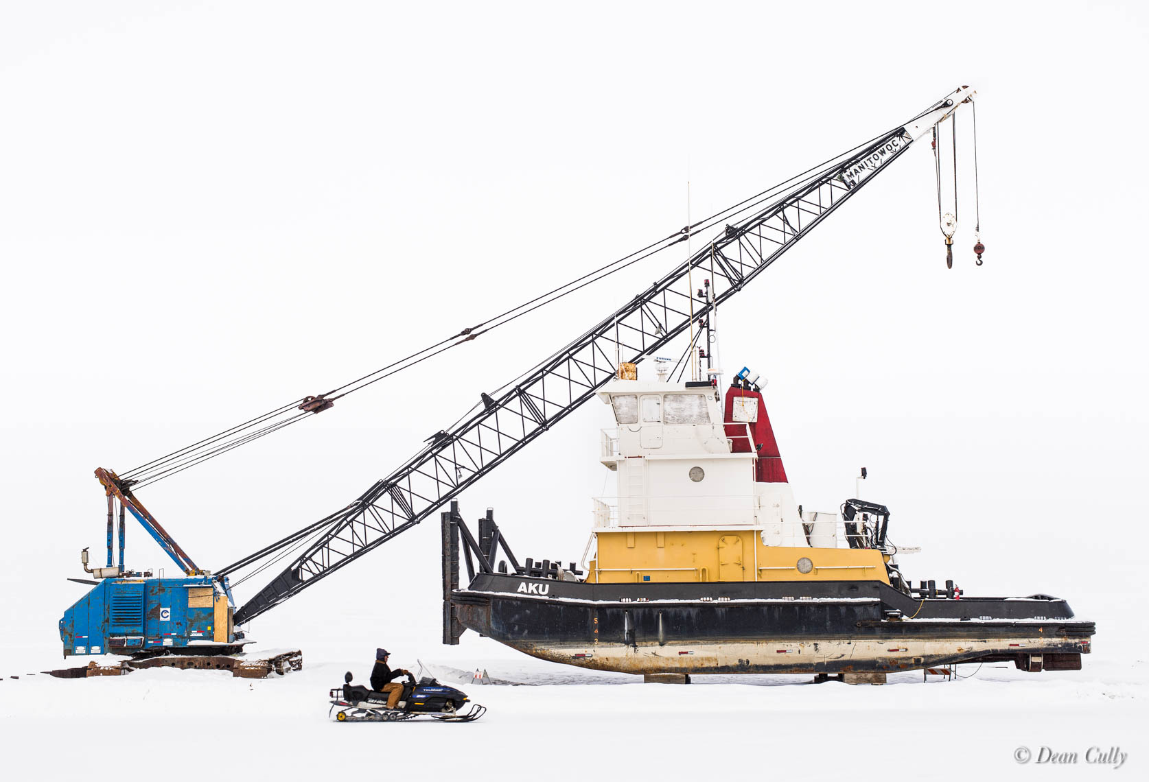 Kotzebue Still-Life with Snowmachine: crane, snowmobile and tugboat in whiteout repose;  northwestern Alaska